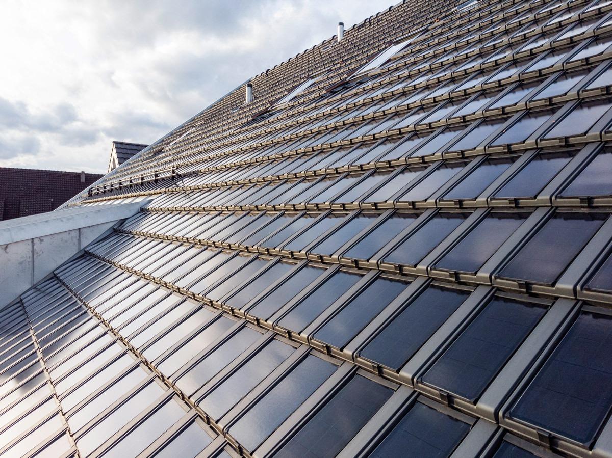 Aussenansicht des Daches eines Mehrfamilienhauses in Regensdorf mit Photovolataiksdachziegel Panotron von Gasser Ceramic