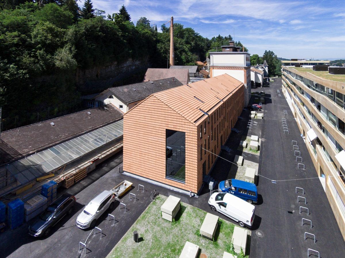 Aussenansicht Gewerbeneubau Gurtenareal Wabern. Das Gebäude (Dach und Wände) ist komplett eingedeckt mit Flachschiebeziegeln von Gasser Ceramic.