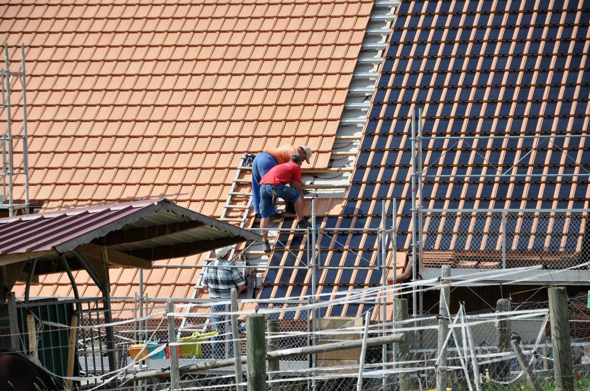 Dachdecker beim Verlegen Panotron Photovoltaikziegeln von Gasser Ceramic auf einem Wohnhaus in Alterswil