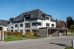 Aussenansicht einer Wohnüberbauung in Kiesen in Bern, deren Dächer mit Flachschiebeziegeln von Gasser Ceramic eingedeckt sind.