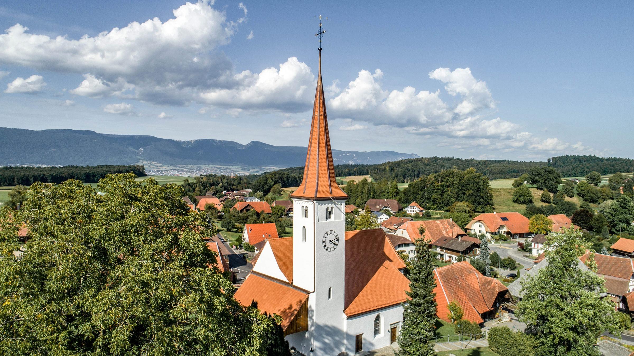Drohnenaufnahme der Kirche Oberwil, die mit 24'400 Stück Biberschwanzziegel Berner Biber, spitz, naturrot von Gasser Ceramic eingedeckt ist.