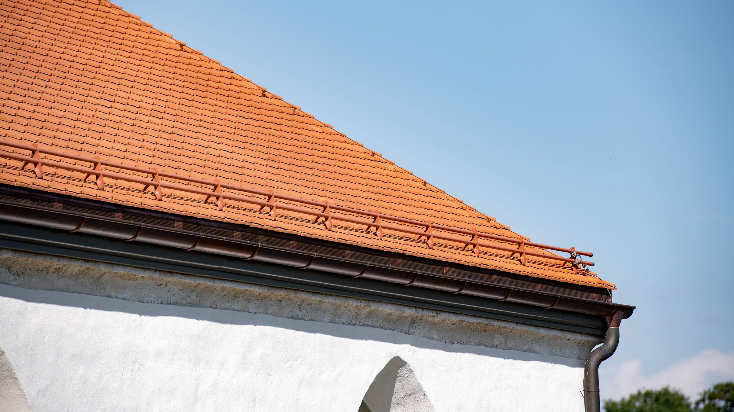 Foto der Kirche Oberwil, die mit 24'400 Stück Biberschwanzziegel Berner Biber, spitz, naturrot von Gasser Ceramic eingedeckt ist.