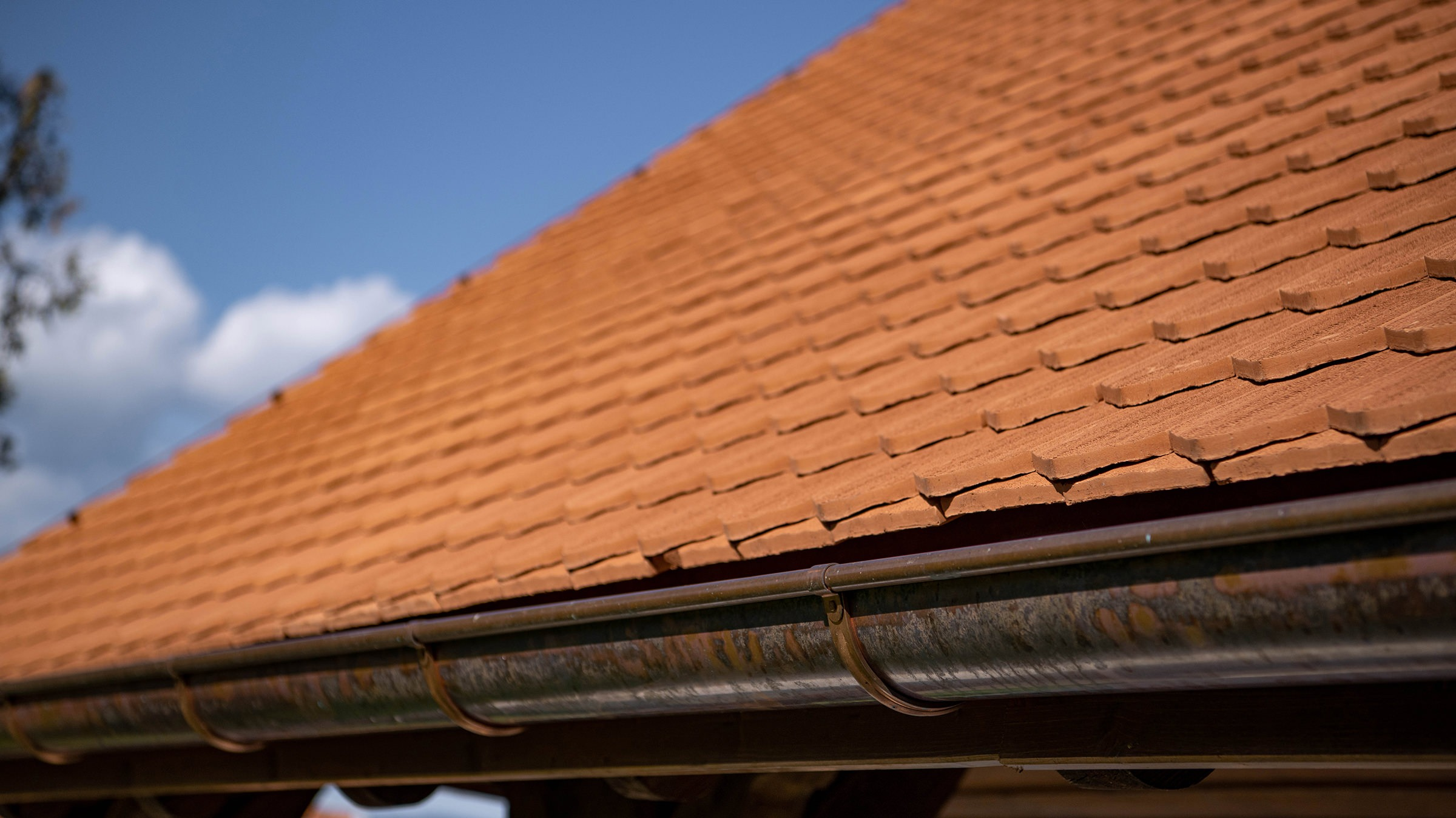 Detailaufnahme vom Dach der Kirche Oberwil, die mit 24'400 Stück Biberschwanzziegel Berner Biber, spitz, naturrot von Gasser Ceramic eingedeckt ist.
