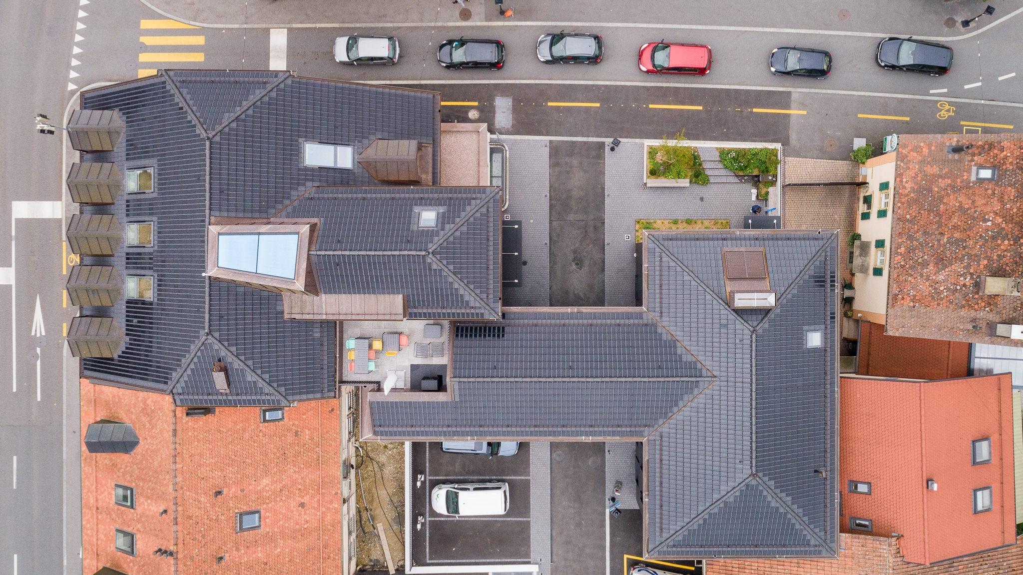 Raiffeisen Gros de Vaud, Echallens, eingedeckt mit Photovoltaik PAN 32 Dachziegeln von Gasser Ceramic, Aussenaufnahme